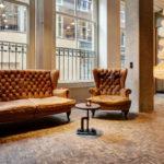 divano e poltrona chippendale nella hall dell'hotel stile vintage V Nesplein in Amsterdam